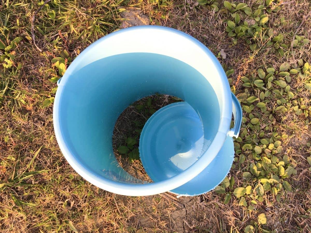 ノコギリでバケツの底に穴を開ける。土嚢制作の道具づくり