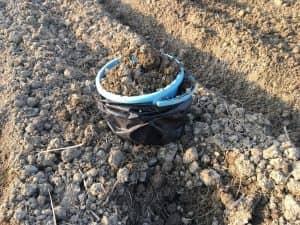 土嚢に設置したバケツに、土を入れる